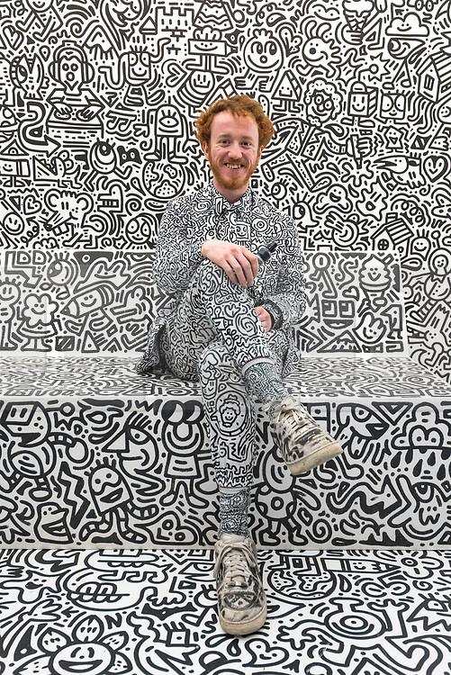 "© Licensed to London News Pictures. 07/04/2018. LONDON, UK. The artist Mr Doodle poses againts his distinctive artwork in The Doodle Room at ""Sense of Space"", an art pop-up which has opened to the public in Broadgate.  Comprising four rooms to challenge the visitor's sensory perceptions through art, the installation is open until 18 May.  Photo credit: Stephen Chung/LNP"