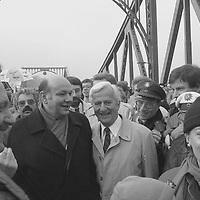 """Bundespräsident Richard von Weizsäcker und der Regierende Bürgermeister von Berlin Walter Momper, gefolgt von Tausenden DDR-Bürgern zu Fuß über die Glienicker Brücke, dem Bauwerk an der Grenze, an dem häufig während des Kalten Krieges der Austausch von Spionen und Gefangenen stattfand. Die bärtigen Herren sorgen für die Sicherheit des hohen Besuchs. Das Lachen der Politiker ist fast diebisch, als wollten sie in Richtung DDR-Führung sagen: """"Seht Ihr, jetzt haben wir es doch geschafft, Euch das Volk wegzunehmen."""""""