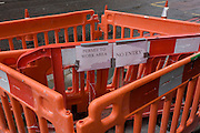 Permit to Work and No Entry notices in construction barriers, in a south London street.