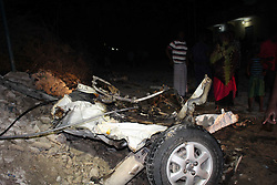 MOGADISHU, Oct. 23, 2016 (Xinhua) -- Residents look at the wreckage of the suicide car in Mogadishu, capital of Somalia, Oct. 23, 2016. A suicide car bomber killed two people and injured four others on Sunday evening in the Somali capital Mogadishu, a local official said.(Xinhua/Faisal Isse) (Credit Image: © Faisal Isse/Xinhua via ZUMA Wire)