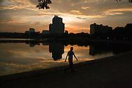 A Vietnamese man walks alongside Giang Vo lake at sunset, Hanoi, Vietnam, Southeast Asia