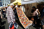 Rug salesman at Portobello Road Market in Notting Hill, West London, England, United Kingdom. People enjoying a sunny day out hanging out at the famous Sunday market, when the antique stalls line the street.  Portobello Market is the worlds largest antiques market with over 1,000 dealers selling every kind of antique and collectible. Visitors flock from all over the world to walk along one of Londons best loved streets.