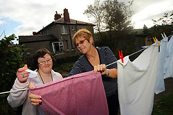 A woman with Learning disabilities hangs out her washing in the garden of her supported flat with her support worker; Skipton; North Yorkshire