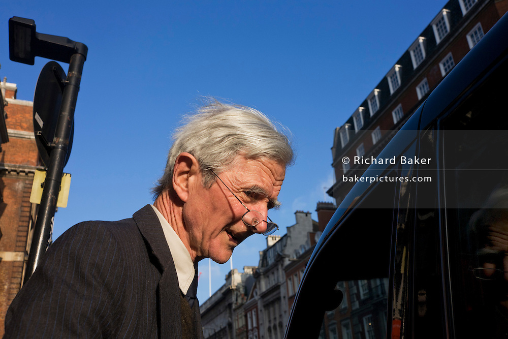 An elderly man emerges from a central London building and nears a taxi cab.
