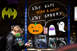 © Licensed to London News Pictures. 16/10/2020. Manchester, UK. A woman wearing face masks walks past a Halloween themed sign in a shop window in Manchester, reminding customers to wear a mask. Manchester is on the verge of a Tier 3 lockdown. Photo credit: Kerry Elsworth/LNP