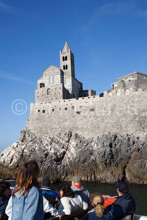 Tourists on a boat looking at the church of Portovenere, Italy.