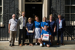 NHS workers from the grassroots NHSPay15 campaign, supported by former Labour Party leader Jeremy Corbyn and MPs Lloyd Russell-Moyle and Ian Byrne, pose outside 10 Downing Street before presenting Matthew Tovey's petition signed by over 800,000 people calling for a 15% pay rise for NHS workers on 20th July 2021 in London, United Kingdom. At the time of presentation of the petition, the government was believed to be preparing to offer NHS workers a 3% pay rise in 'recognition of the unique impact of the pandemic on the NHS'.