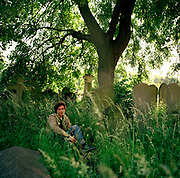 Greek-born writer of foward-fiction, Panos Karnezis in London where he lives and writes. Here, he is a west London cemetery, relaxing in long grass amid Victorian headstones. The light is back-lighting this seemingly rural landscape. Author of Little Infamies (2002), The Maze (2004) and the Convent (2010) he is a developing writer of prize-winning fiction, shortlisted for the Whitbread First Novel for the acclaimed Little Infamies. Panos Karnezis was born in Greece in 1967 and came to England in 1992. He studied engineering and worked in industry, then studied for an MA in Creative Writing at the University of East Anglia.