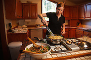 USA, Oregon, Eugene, young woman mixing the linguine into the dinner. MR
