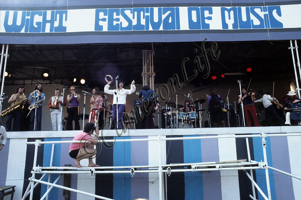 """Lighthouse - the full line-up.- .Lighthouse formed in Toronto, Canada, in 1969. All thirteen members of the band are present here in this photograph. The effect of having so many strings and horns, combined with modern rock, gave a heavy hitting big band sound - their most memorable songs to date being """"One Fine Morning"""" and """"Pretty Lady""""."""