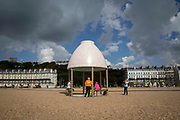 Visitors enjoy sitting inside Lubaina Himid's Jelly Mould Pavilion on Folkestone's sea front as part of the 2017 Folkestone Triennial. Folkestone, Kent.