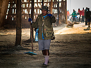 10 FEBRUARY 2016 - BAN LAEM, PHETCHABURI, THAILAND: Workers walk through a salt barn out to the fields at the beginning of the salt harvest in Phetchaburi province, Thailand. The salt harvest in Thailand usually starts in February and continues through May. Salt is harvested in many of the provinces along the coast, but the salt fields in Phetchaburi province are considered the most productive. The salt fields are flooded with sea water, which evaporates off leaving salt behind. Salt production relies on dry weather and producers are hoping the current drought will mean a longer harvest season for them.      PHOTO BY JACK KURTZ
