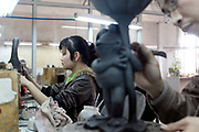 Workers make petroleum resin based gift items and garden ornaments at the Chuan Sen Art & Design Factory on the outskirts of Guangzhou, in Guangdong Province, China on 04 February, 2009.  Orders at the factory, who exports almost all of their wares in North America and Europe, has declined drastically in the last two years due to the economic slowdown and western consumers' belt-tightening.