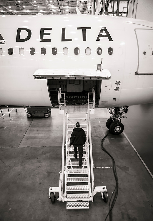 A technician mounts the stairs while conducting a maintenance check at Delta Tech Ops, Atlanta.  <br />