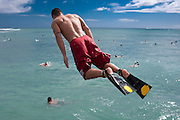 A young man jumps into the ocean with swim fins.
