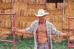 cowboy with an open shirt opening a gate with hay bales