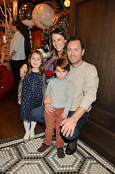 GREGOR & JULIET ANGUS with their children TRUMAN & GEORGINA at a party hosted by Camila Batmanghelidjh for Kids Company held at The Ivy Market Grill, 1 Henrietta Street, Covent Garden, London on 23rd November 2014.