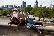 A girl laughs whilst laying on the wall on Tower Bridge, London. A tourist having her photo taken, she was overcome with laughter.