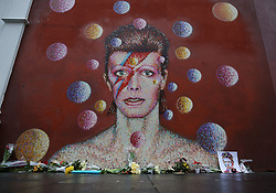 © Licensed to London News Pictures. 11/01/2016. London, UK. Floral tributes are placed at a mural of David Bowie in Brixton. The Death of David Bowie, who was born in Brixton, has been announced today.  Photo credit: Peter Macdiarmid/LNP