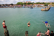 Young people dive jumping off Folkestone Harbour into the sea water after the annual Trawler race and fun day in Folkestone, Kent, England, United Kingdom.  (photo by Andrew Aitchison / In pictures via Getty Images)