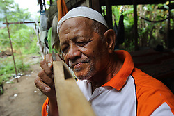 Haji Muhammed  Dahlan 69 years works on some home improvements. He married Nurbaiti, 48 years, after losing his wife in the tsunami. Their house still uses the Oxfam installed gravity flow water system that was fitted in the years just after the Indian Ocean tsunami, Lampuuk village District Aceh Besar, Aceh Province, Sumatra, Indonesia