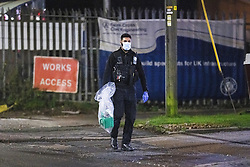 © Licensed to London News Pictures. 14/11/2020. Moston, UK. A green petrol can is removed from the scene , emptied at a nearby petrol station and packaged in to a police evidence bag . Scene on Williams Road in Moston where it's understood a women's body was found on fire earlier this evening (Saturday 14th November 2020) . Photo credit: Joel Goodman/LNP