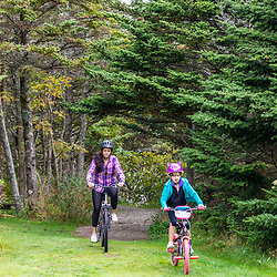 A woman and her daughter ride bikes at Quoddy Head State Park in Lubec, Maine.