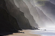 A series of steep cliff ridges in heavy mist along Wildcat Beach, Point Reyes National Seashore, California. The beach can only be hiked at low tide as the waves reach the cliffs at high tide.