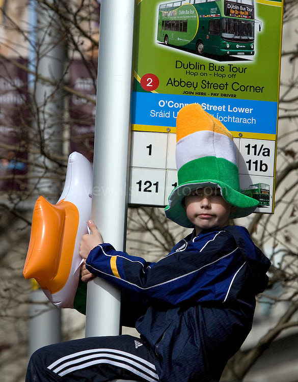 Boy on signpost watching the Dublin St. Patrick's Day parade, wearing an Irish tricolor hat