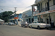Street scene shops, bank, bar tourist and vintage cars, thought to be Port Antonio, Jamaica 1970