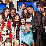 Happy friends help Bat Mitzvah girl light her cake candles