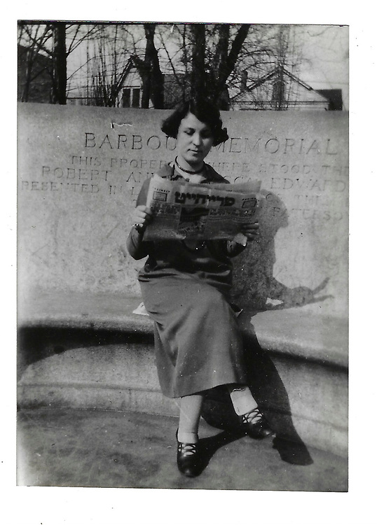 Blank. Esther reading a Hebrew newspaper.