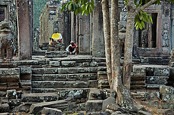 Buddhist nun prepares worship to statue of Buddha at Bayon temple in early morning