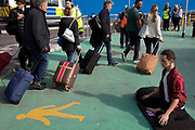 As environmental activists protest about Climate Change during the occupation of City Airport (London's Business Travel hub) in east London, air passengers walk past a young man sitting in the Lotus Position outside the terminal building on the fourth day of a two-week prolonged worldwide protest by members of Extinction Rebellion, on 10th October 2019, in London, England.