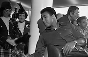 Muhammad Ali In Dublin..1972..11.07.1972..07.11.1972..11th July 1972..Prior to his fight against Al 'Blue' Lewis at Croke Park ,Dublin, former World Heavyweight Champion,Muhammad Ali arrives at Dublin Airport..The fight was part of his build up for for a championship fight against the current World Champion, 'Smokin'  Joe Frazier. Ali had been stripped of the title partly due to his refusal to join the American military during The Vietnam War,which he had opposed...Image of a very relaxed Muhammad Ali as he shows off the Shilleagh to some of The Emerald Girls Pipe Band