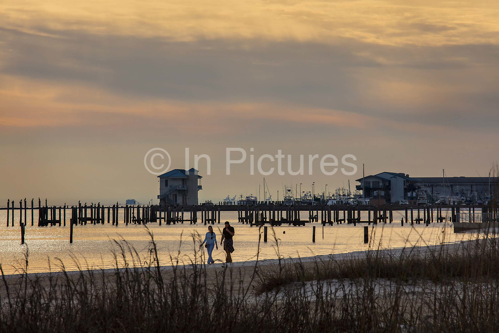 Couple walking on the white sands at sunset on 6th March 2020 on 8th March, 2020 in Biloxi, Mississippi, United States.