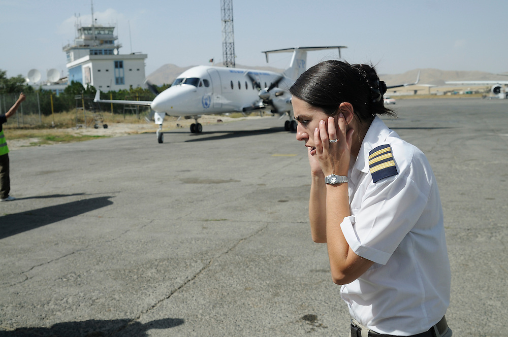 """Pilot, Danielle Aitchison, covers her ears while an UNHAS Beechcraft 1900D taxis at Kabul International Airport.  Danielle flies in Afghanistan for The United Nations Humanitarian Air Service (UNHAS).   .. ...When asked about flying in a war zone, she says,  """"I'm just a normal average female.  My job is maybe a little different to some, but I have the same feminine side as other women.  I don't have any trouble going back to New Zealand relating to people.  I'm just a regular chick.""""."""