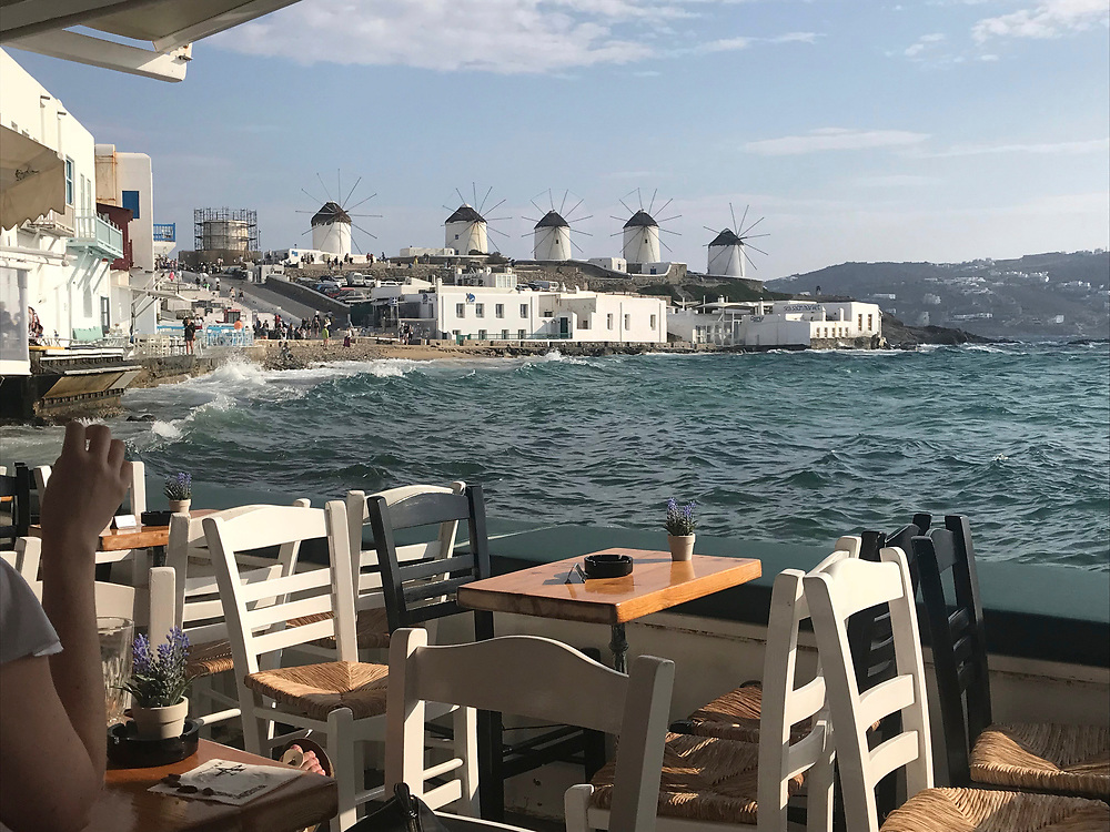 Famous Mykonos windmills in the distance as seen from a restaurant in the harbor