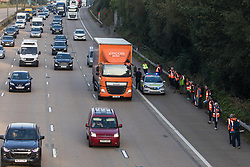 Ockham, UK. 21st September, 2021. Insulate Britain climate activists prepare to block the anticlockwise carriageway of the M25 between Junctions 9 and 10 as part of a campaign intended to push the UK government to make significant legislative change to start lowering emissions. The activists briefly halted traffic on both carriageways before being removed and arrested by Surrey Police.