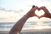 Hand gesture forming a heart shape for Love