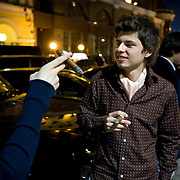 Wealthy youngsters, aged 17, smoke cigars outside a fancy bar in Moscow.