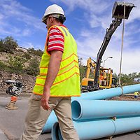 062614       Cable Hoover<br /> <br /> Contractors lift a section of new piping into a trench along Grandview Drive in Gallup Thursday. Century Club Construction is replacing the outdated iron water main with new PVC lines.