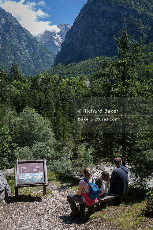With the highest peaks in Slovenia in the distance a family admire the view of the highest peaks in the Slovenian Julian Alps, on 22nd June 2018, in Trenta, Triglav National Park, Slovenia. Beyond are the mountains, Kreiski 2050m, Pihavec 2419m, Dolina Zadnjica and Triglav 2864m.