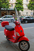 Red scooter, or Vespa, in the heart of Rome, Italy