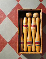 Antique wooden bowling game on painted canvas rug