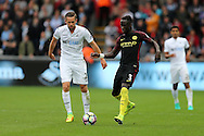 Bacary Sagna of Manchester city in action as Gylfi Sigurdsson of Swansea city looks on. Premier league match, Swansea city v Manchester city at the Liberty Stadium in Swansea, South Wales on Saturday 24th September 2016.<br /> pic by Andrew Orchard, Andrew Orchard sports photography.