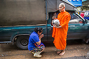 "03 OCTOBER 2012 - BANGKOK, THAILAND:    A Buddhist monk collects alms from a vendor in Khlong Toey Market in Bangkok. Khlong Toey (also called Khlong Toei) Market is one of the largest ""wet markets"" in Thailand. Thousands of people shop in the sprawling market for fresh fruits and vegetables as well meat, fish and poultry every day.      PHOTO BY JACK KURTZ"