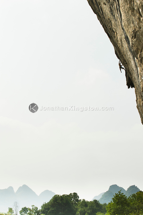 A rock climber scales a steep cliff known as The White Mountain on a route known as Chinaclimb in Yangshuo, China (Model Released, Lau Siu Kei Gary).