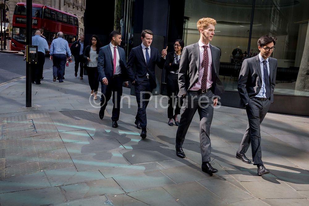 Londoners walk through reflected light at lunchtime on Threadneedle Street in the City of London, the capitals financial district also known as the Square Mile, on 6th April 2017, in London, England.