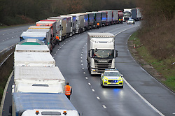 © Licensed to London News Pictures 22/12/2020.        Ashford, UK. Lorry being escorted out of the queue by police. Hundreds of freight lorries remain stranded on the M20 in Kent today as France keep their borders closed due to fears over the new Cornavirus strain. Photo credit:Grant Falvey/LNP